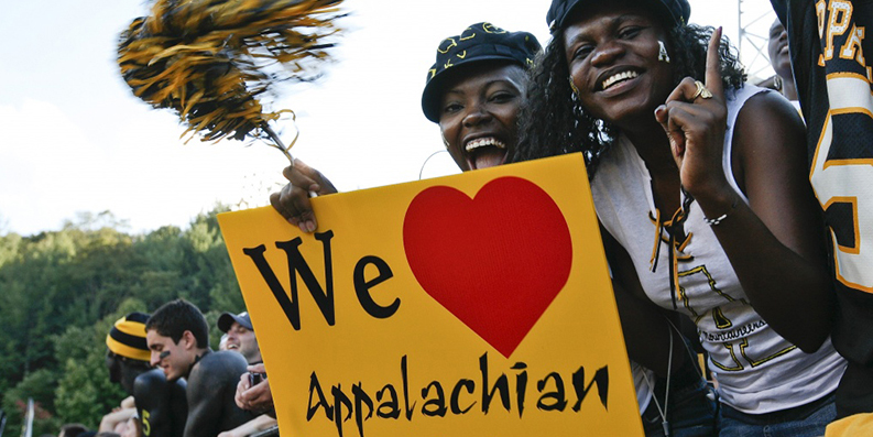 Students at Appalachian football game with painted faces and pompom